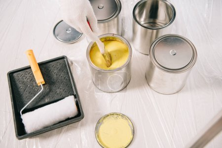 Photo pour Cropped view of man dipping paintbrush into can with yellow paint - image libre de droit