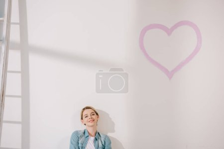 Photo pour Happy young woman sitting on floor near white wall with painted pink heart - image libre de droit