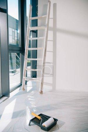 Photo pour Pièce avec grande fenêtre, échelle près du mur blanc, rouleau à peinture dans le plateau à rouleaux sur le sol recouvert de cellophane - image libre de droit