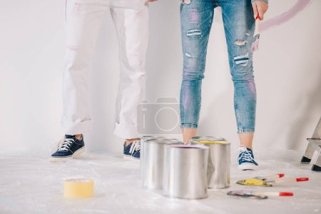 Photo pour Cropped view of man and woman standing by white wall near cans with paint - image libre de droit