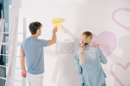 Photo pour Man painting white wall in yellow while girlfriend drawing pink heart - image libre de droit