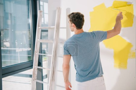 Foto de Back view of young man painting white wall in yellow with paint roller - Imagen libre de derechos