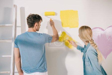 Photo pour Jeune couple peignant un mur blanc en jaune avec des rouleaux à peinture - image libre de droit