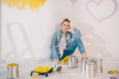 Photo pour Attractive young woman holding yellow paint roller while sitting on floor near wall - image libre de droit