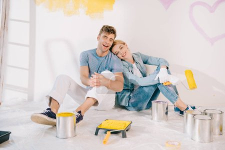 Photo pour Happy young woman holding yellow paint roller while sitting on floor near boyfriend - image libre de droit