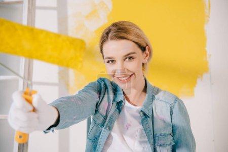 Photo pour Foyer sélectif de jolie jeune femme tenant rouleau de peinture jaune et souriant à la caméra - image libre de droit