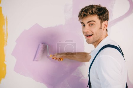 Photo pour Handsome young painter painting wall in pink color with paint roller and smiling at camera - image libre de droit