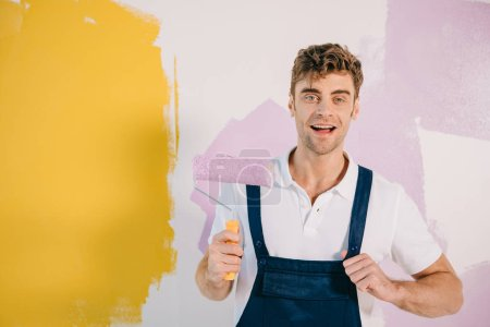 Foto de Handsome young painter in overalls holding paint roller while standing near wall painted in yellow and pink - Imagen libre de derechos