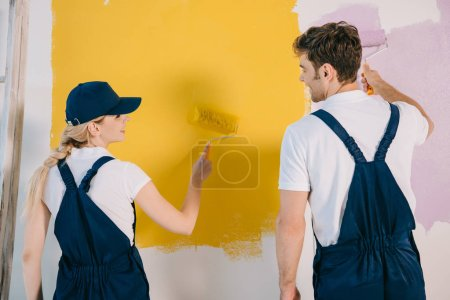Foto de Young painters in uniform looking at each other while painting wall in yellow and pink - Imagen libre de derechos