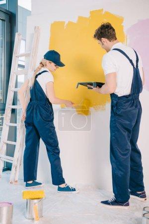 Photo pour Jeune peintre tenant un plateau à rouleaux tout en attrayant collègue peignant un mur avec rouleau à peintures - image libre de droit