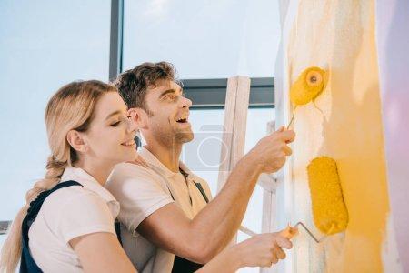 Foto de Dos jóvenes pintores sonriendo mientras pintaban paredes con rodillos de pintura. - Imagen libre de derechos