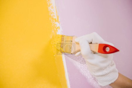 Photo pour Partial view of painter painting wall in yellow and pink with paintbrush - image libre de droit