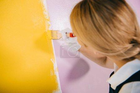 Photo pour Retour de la peinture murale d'un jeune peintre en jaune et rose avec pinceau - image libre de droit