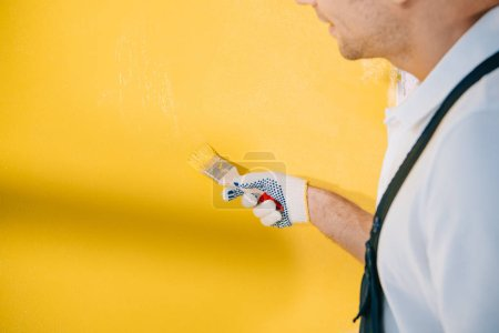 Photo pour Cropped view of young painter painting wall in yellow color with paintbrush - image libre de droit