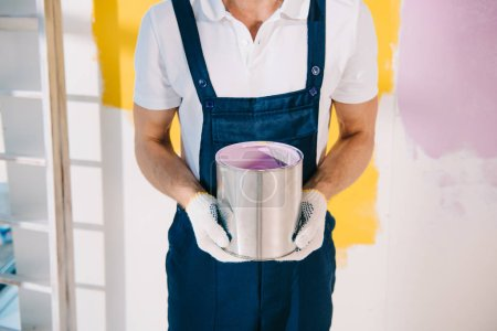cropped view of painter in uniform holding can with paint