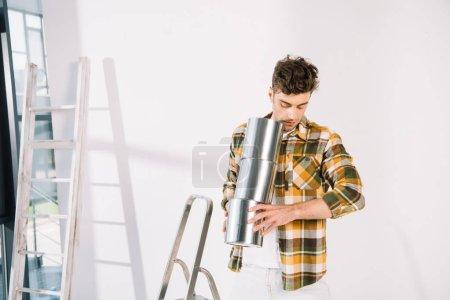 Photo pour Beau jeune homme tenant des canettes avec de la peinture tout en se tenant près du mur blanc - image libre de droit