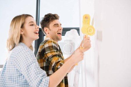 Photo pour Un jeune couple heureux peignant un mur blanc en jaune avec des rouleaux à peinture - image libre de droit