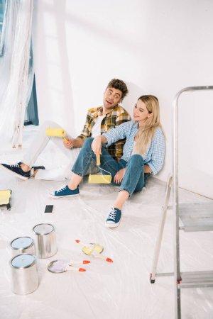 Photo pour Un jeune couple gai assis près d'un mur blanc et tenant des rouleaux à peinture jaunes - image libre de droit