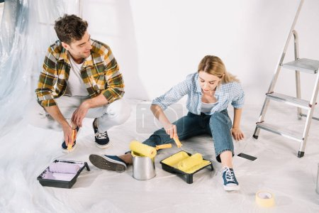 Photo pour Handsome man holding pink paint roller and woman putting paint roller into yellow paint while sitting on floor - image libre de droit
