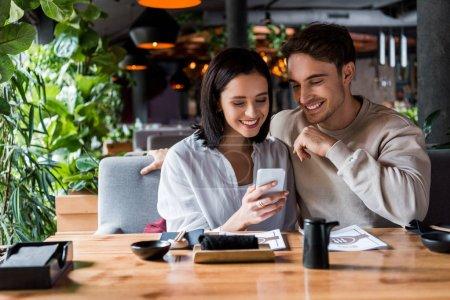 Photo pour Heureux homme et femme regardant smartphone dans le bar à sushi - image libre de droit