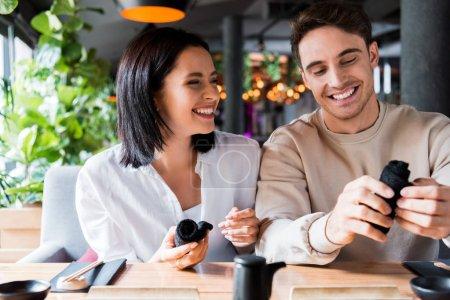Photo pour Homme et femme joyeux tenant des serviettes noires dans le bar à sushi - image libre de droit