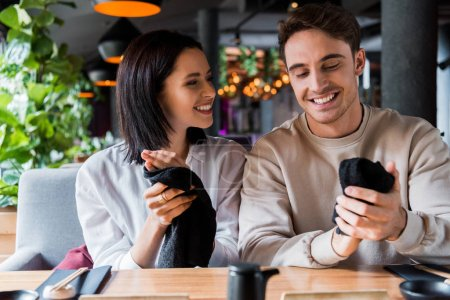 Photo for Cheerful man and happy woman holding black napkins in sushi bar - Royalty Free Image