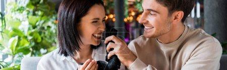 Photo pour Plan panoramique de l'homme heureux tenant une serviette noire près d'une femme souriante - image libre de droit