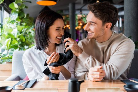 Photo pour Homme heureux tenant serviette noire près du visage de la femme souriante - image libre de droit