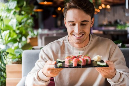 Photo for Happy man looking at plate with tasty sushi in restaurant - Royalty Free Image