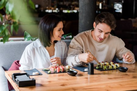 Photo for Selective focus of happy man and woman near tasty sushi in restaurant - Royalty Free Image