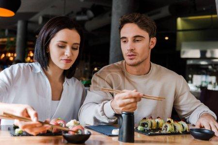 Selektiver Fokus der attraktiven Frau mit Essstäbchen und leckerem Sushi in der Nähe des Mannes im Restaurant