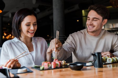 Photo for Selective focus of happy woman holding chopsticks with tasty sushi near handsome man in restaurant - Royalty Free Image