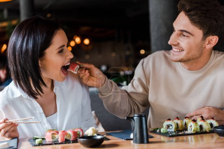 Photo for Selective focus of happy man holding chopsticks with tasty sushi near young woman in restaurant - Royalty Free Image