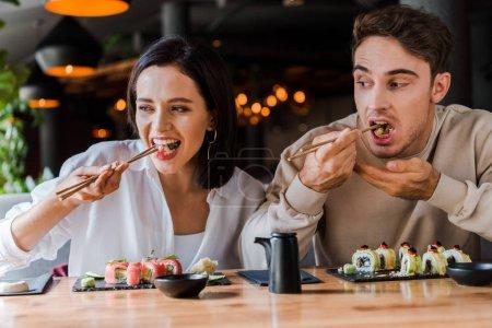 Photo pour Un jeune homme et une jeune femme mangent de savoureux sushis dans un bar à sushis - image libre de droit