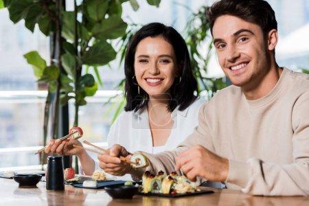 glücklicher Mann und Mädchen mit Essstäbchen und Sushi im Restaurant