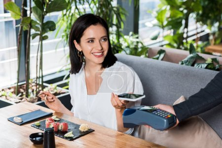 Photo for Cropped view of waiter holding credit card reader near cheerful woman paying with smartphone - Royalty Free Image