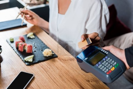 cropped view of waiter holding credit card reader near woman paying with credit card