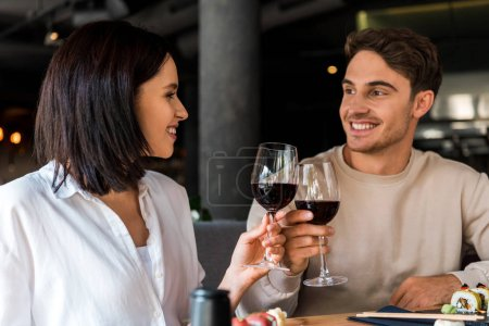 happy man and cheerful woman clinking glasses with red wine near sushi