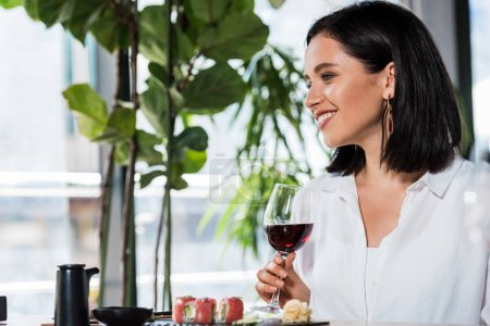 Photo for Happy woman holding glass with red wine near tasty meal in sushi bar - Royalty Free Image
