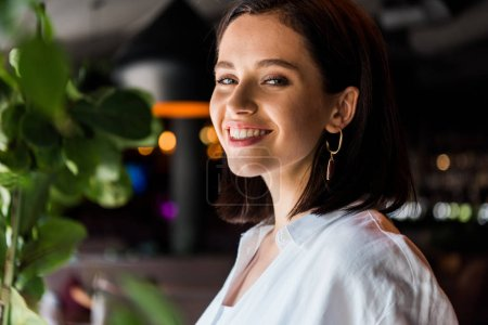 Photo for Cheerful young woman looking at camera in restaurant - Royalty Free Image