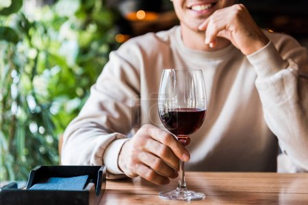 Photo for Cropped view of cheerful man sitting in restaurant with glass of wine - Royalty Free Image