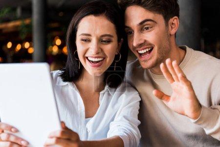 Photo pour Femme heureuse regardant tablette numérique près de l'homme joyeux agitant la main - image libre de droit