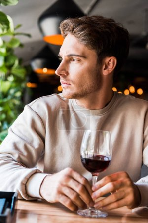 selective focus of handsome man sitting in restaurant with glass of wine
