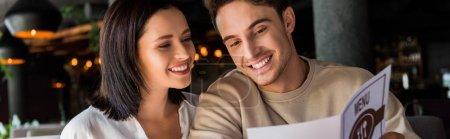 Photo pour Plan panoramique de l'homme et de la femme heureux regardant le menu - image libre de droit