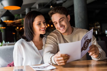 Photo for Happy man and woman looking at menu in restaurant - Royalty Free Image
