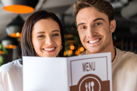 Photo for Selective focus of happy man and woman holding menu - Royalty Free Image