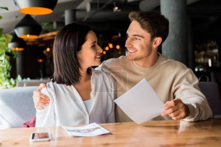 Photo for Selective focus of happy man and woman smiling in restaurant - Royalty Free Image
