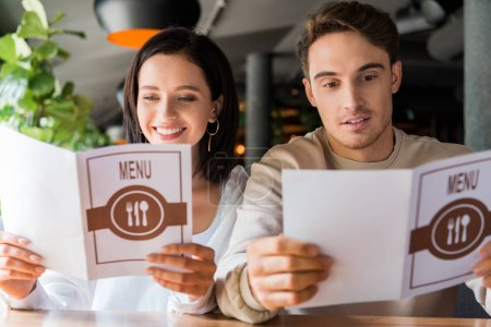 Photo pour Foyer sélectif de l'homme heureux et souriante femme regardant les menus dans le restaurant - image libre de droit