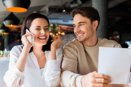 Photo for Selective focus of happy man near cheerful woman talking on smartphone - Royalty Free Image