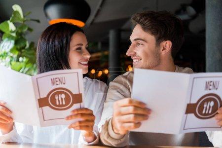 Photo pour Homme et femme heureux se regardant en tenant des menus au restaurant - image libre de droit